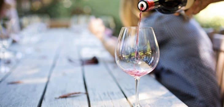 wine tasting venue with wine being poured into a glass on a wooden table